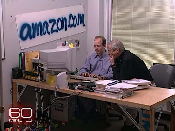 ο Jeff Bezos, το 1999, σε ένα μικρό γραφειάκι με το λογότυπο Amazon γραμμένο με σπρέι στον τοίχο